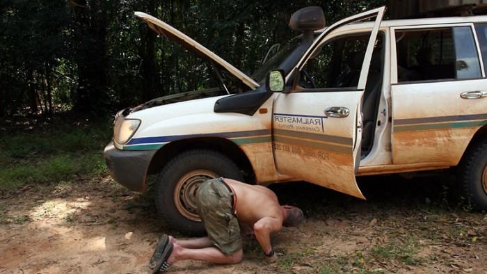 Человек пытается починить автомобиль